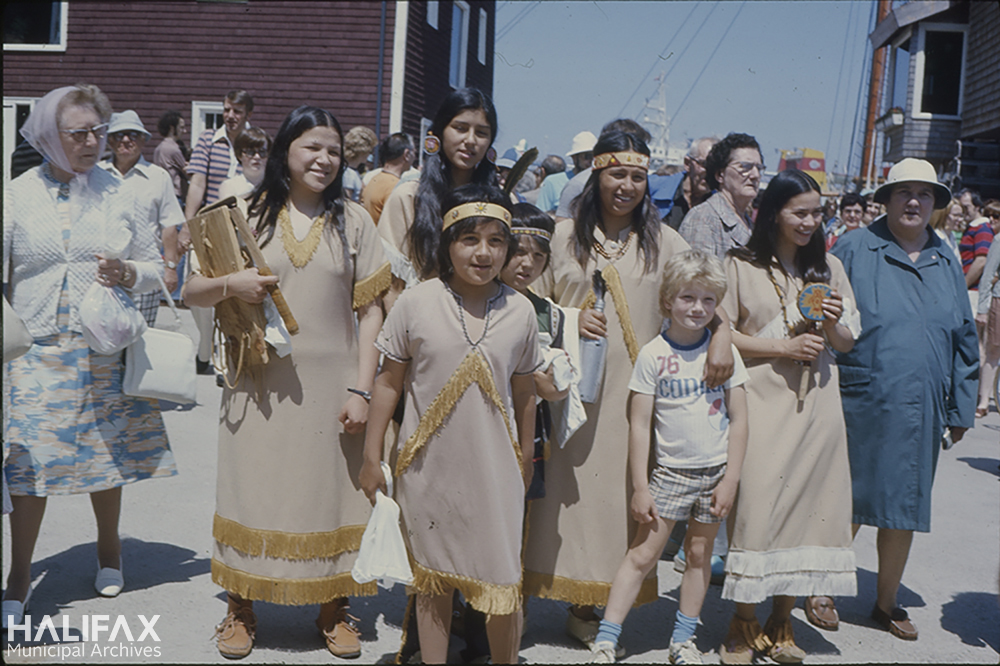 Image of a group of Mi'kmaq people in traditional dress posing with a family during Natal Day celebrations on the Halifax waterfront