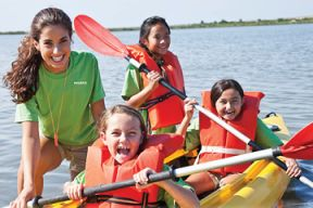 An instructor and group of children in kayaks on lake