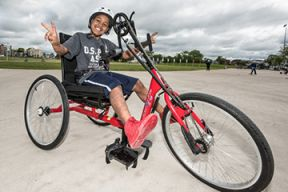 A young boy on an adaptive bicycle on the Emera Oval