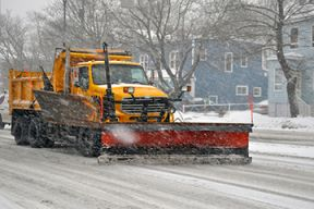 A snow blow drives down a snowy street clearing the way for vehicles.