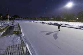 The Emera Oval at night with a single skater on the ice