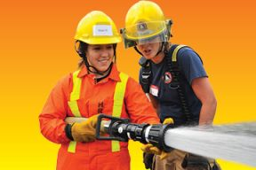 Two young women in fire fighter gear hold a fire hose during a training exercise.