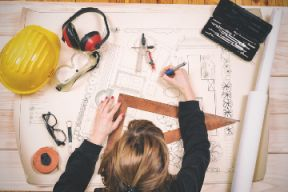 A female architect or engineering is sitting at her desk and drafting.