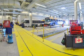 The interior of the Ragged Lake Bus Garage shows buses ready for maintenance in the background