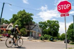 A cyclist stops at a Stop Sign on a side street in Halifax. It is a sunny day and there is as lot of greenery present.