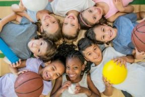 kids sitting in a circle holding sport equipment