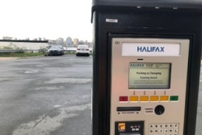 "A close-up of a new parking pay station. Screen reads ""Parking is changing, coming soon!"". The Halifax skyline is in the background"