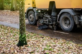 An image of a street cleaner machine sweeping leaves along the side of the street.