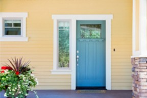 A blue front door contrasts against a bright yellow house.