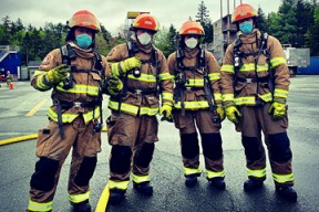Four volunteer firefighters stand together wearing their fire gear and masks during Covid.
