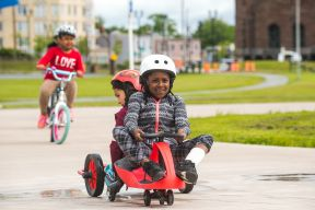 Children using plasma cars and bikes at the Emera Oval