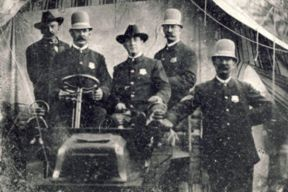Black and white historic posed photo of a uniformed officer sitting in a car with four uniformed officers standing beside the car.