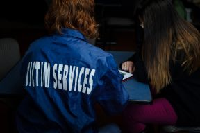 Photo taken from behind of Victim Services volunteer wearing a navy blue jacket with Victim Service in white lettering on the back.
