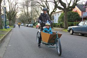 A father and son travel by cargo bicycle down a local street bikeway