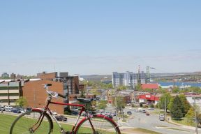 A red bike sites on Citadel Hill with Halifax in the background