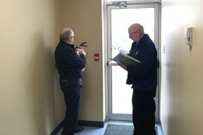Image of two Halifax Regional Fire & Emergency Fire Prevention Officers conducting an inspection of a building. One is looking closely at a portable fire extinguisher while the other makes notes.