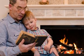 Image of a Grandfather reading a book to his Grandson sitting on his lap in front of a fire.