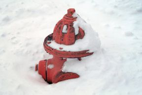 Close up image of a red fire hydrant buried in snow about half of the way up.