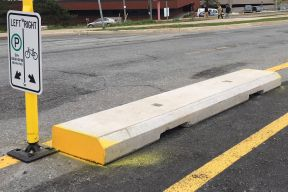 Concrete curbs used to separate people cycling from vehicle traffic on Rainnie Drive
