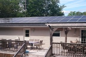Multiple solar panels on a house roof house has large deck with lots of deck furniture