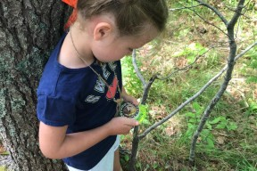 a child looks at a compass