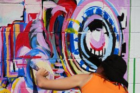 artist paints a colourful abstract design on a wall