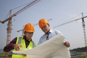 Two employees look at a blueprint with construction cranes in the background