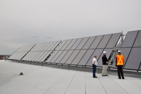 three employees stand next to very large solar panels on the top of a building