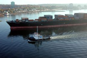 a tugboat accompanies a large container ship in the Halifax Harbour