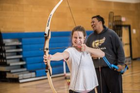A woman practices archery in a gym