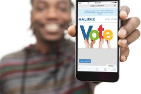 A person holds a phone, signifying that a user can e-vote in the municipal election.
