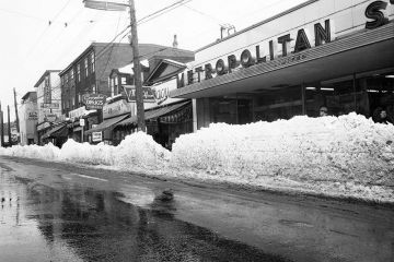 Black and white image of the east side of Gottingen Street, after a heavy snowfall in February 1960.  Shows Metropolitan Stores, J. Macy Co. Ltd. ladies wear, Coombes Drug Store and Luncheonette, Withrows Drugs, and [Allen and Son Ltd. hardware