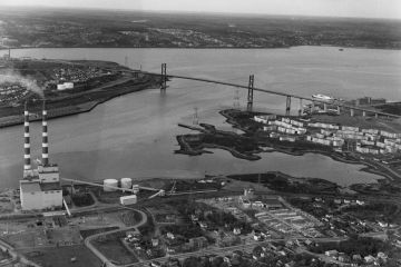 Black and white oblique aerial photograph looking northwest from Windmill Road towards the narrows and MacKay Bridge, showing 2 stacks at the Tuft's Cove generating Station, Shannon Park the Bedford Institute of Oceanography and across the Harbour to a demolished Africville and the Rockhead city prison lands. Photograph by Atlantic Air Survey.