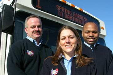 Three transit operators stand in front of a bus