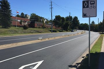 Mumford Road painted with the transit priority diamond and a sign explaining how the road works