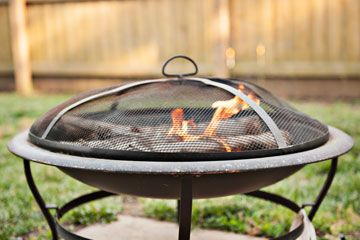 Close up image of a round metal outdoor wood burning appliance with a small fire burning covered by a screen spark arrestor
