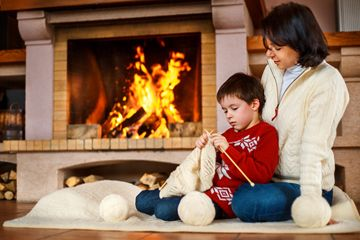 A mother and her young son sit in front of their fire place on the floor. The little boy is learning to knit.